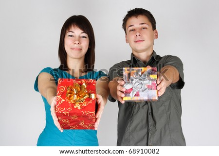 young brunette girl and man offer gifts to camera and smiling - stock photo