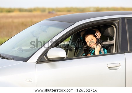 young brunette girl behind  wheel throws  belt - stock photo
