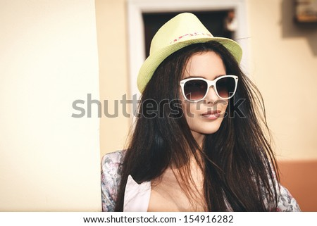 Young brunette girl closeup portrait. Stylish woman posing on the street with interested look and green hat on her head. - stock photo
