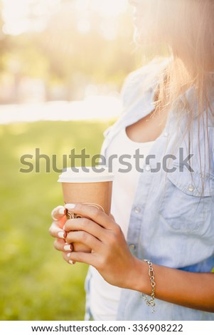 young brunette girl drinking hot coffee in the morning cappuccino on the street,Fashion portrait of sexy woman face with perfect skin and gores full red lips, wearing trendy summer elegant outfit.