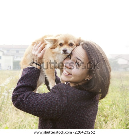young brunette girl hugging her little dog with a grassy field in the background - stock photo