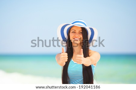 Young brunette girl on the beach in summer time. - stock photo