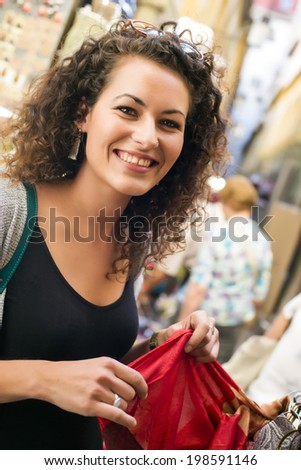 Young brunette girl shopping some clothes in an exotic market - stock photo