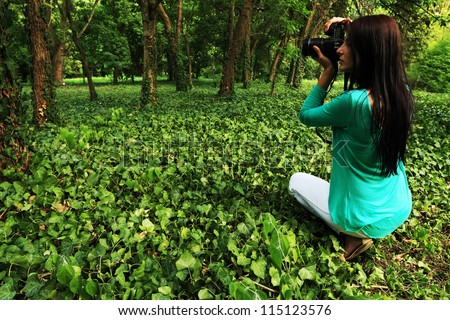 Young brunette girl taking nature photos - stock photo