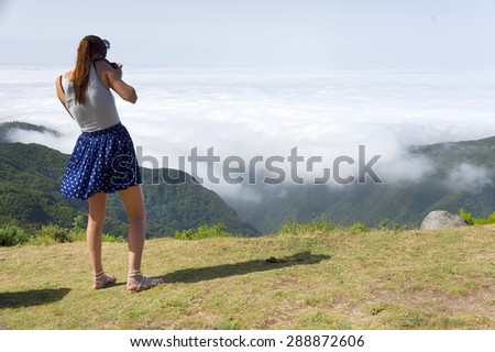 Young brunette girl taking photos of the mountain scenery, Madeira, Portugal - stock photo