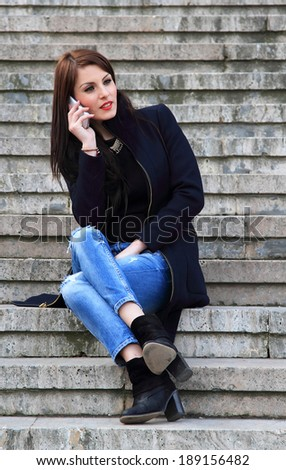 Young brunette girl using a mobile phone