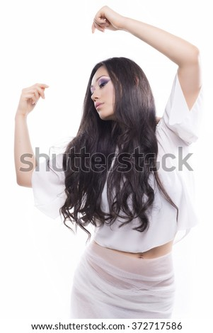 Young brunette girl white dressed on white background dancing