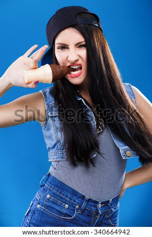 Young brunette girl, with long dark hair, wearing in striped shirt, jeans, cap and waistcoat, holding plastic ice cream in her mouth, on blue background, in studio, waist up - stock photo