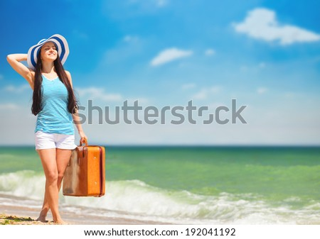 Young brunette girl with suitcase on the beach in summer time. - stock photo