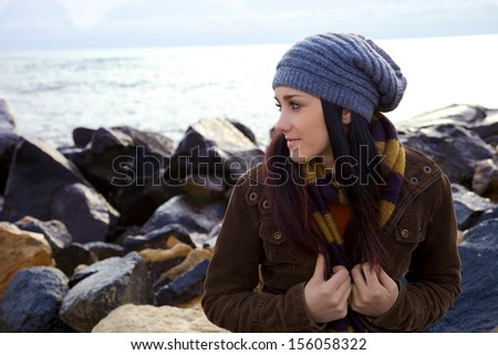 Young brunette in autumn thinking on the beach