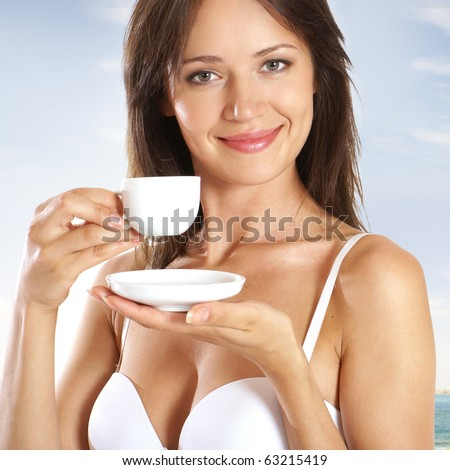Young brunette in sexy lingerie drinking morning coffee over resort background - stock photo