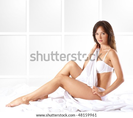 Young brunette in sexy lingerie  isolated on white - stock photo