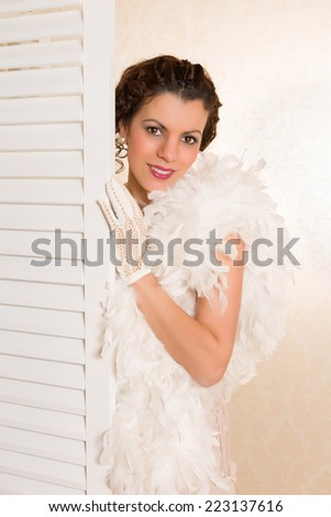 Young brunette in vintage 1920s feather boa looking from behind a folding screen in her boudoir - stock photo