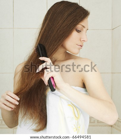 Young brunette lady combing her beautiful long hair in a bathroom. similar image - stock photo