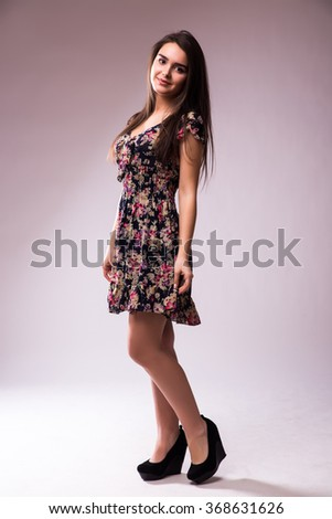 Young brunette lady in  dress posing on grey background