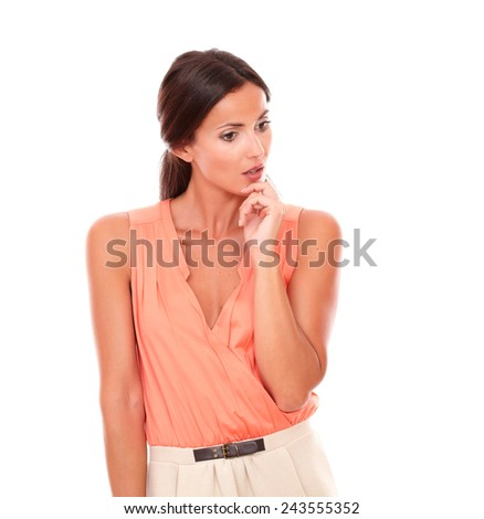 Young brunette lady looking down wondering about a question with hand on chin while standing in white background - copyspace - stock photo