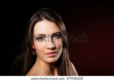 Young brunette lady posing on dark background
