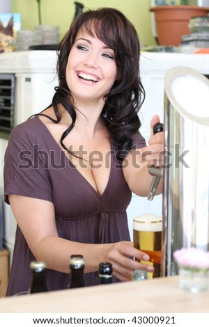 young brunette landlady in a pub draws beer at the bar