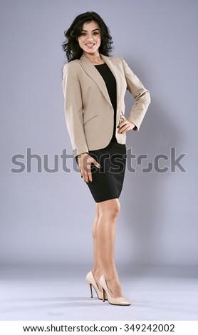 Young brunette latin businesswoman, full length portrait on gray - stock photo
