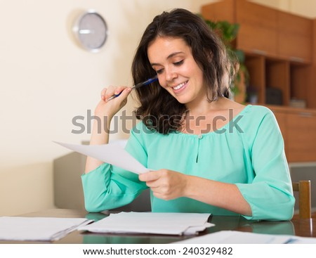 Young brunette long-haired woman filling in paper at home - stock photo