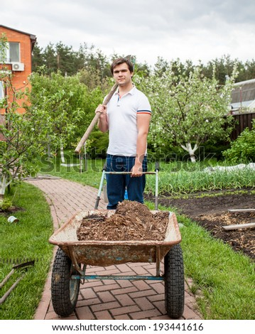 Young brunette man holding shovel and wheelbarrow