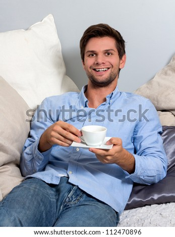 Young brunette man in blue clothing  enjoying a coffee break - stock photo
