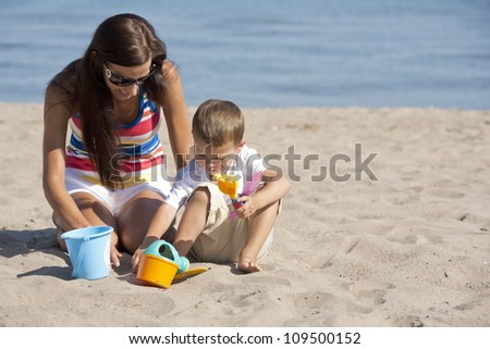 young brunette modther holding her little son outdoors