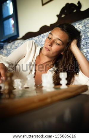 Young brunette playing chess - stock photo