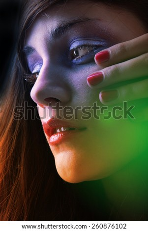 Young brunette portrait with multicolor light - stock photo