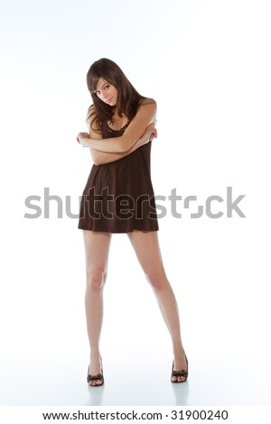 Young brunette posing in little brown dress . Isolated over white background