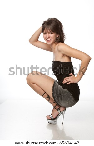 young brunette posing in short skirt isolated over white background