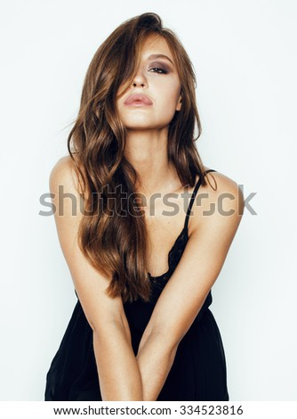 young brunette pretty woman in black dress posing on white background with make up sexy - stock photo