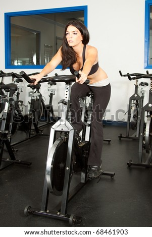 young brunette riding a bike at the gym - stock photo