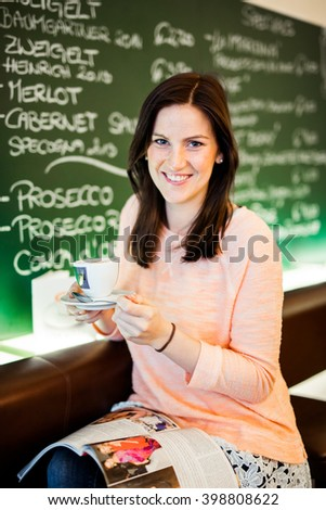 Young brunette smiling and happy woman sitting at a coffeeshop relaxing with her Cappuccino / Coffee - stock photo
