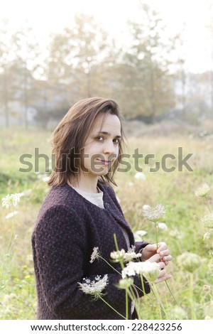 young brunette smiling woman picking wildflowers in the countryside with sunlight - stock photo