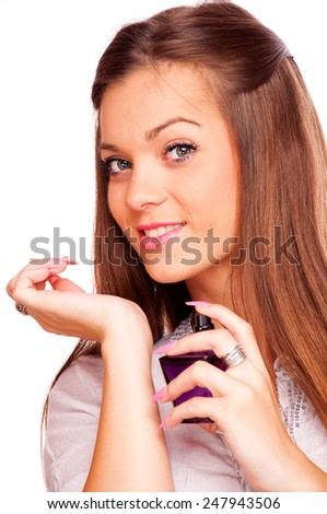 Young brunette spraying perfume on her hand and looking at camera, isolated on white - stock photo