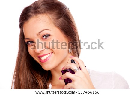 Young brunette spraying perfume on her neck and looking at camera, isolated on white - stock photo