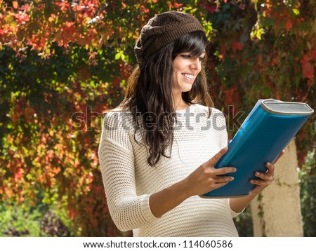 Young brunette studying and reviewing the lesson on autumn park background