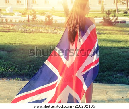 Young brunette warped in Great Britain flag like cloak from back view - stock photo