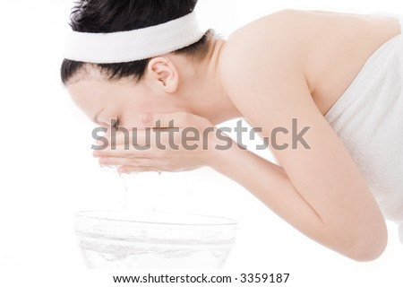young brunette washing her face, studio white - stock photo