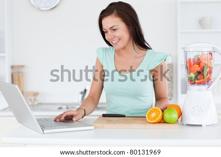 Young brunette with a laptop and fruits in her kitchen