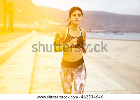 Young brunette with earphones running with palm trees and a mountain behind her while wearing casual clothes and looking ahead