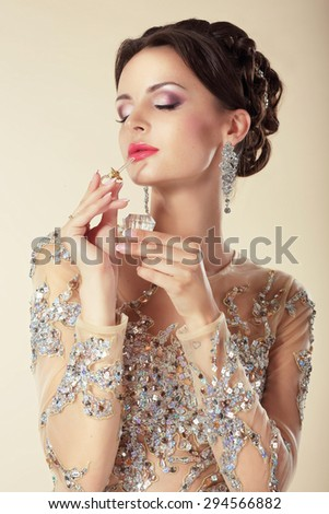 Young Brunette with Perfume Bottle. Fragrance - stock photo