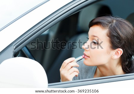 Young brunette woman applying makeup while in the car  - stock photo