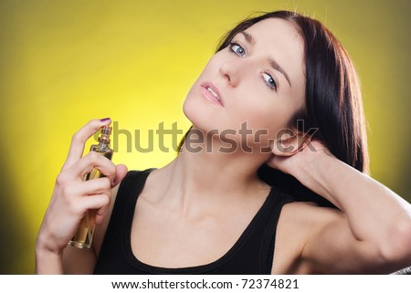 Young brunette woman applying perfume on her body - stock photo
