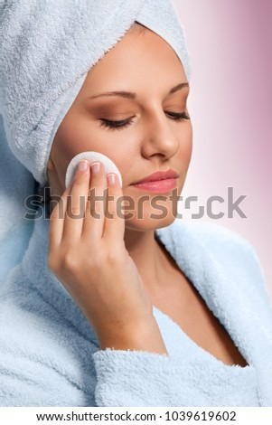 Young brunette woman cleaning her face with cotton pad. Skincare concept.