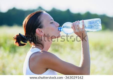 Young brunette woman drinking water during morning jogging. - stock photo