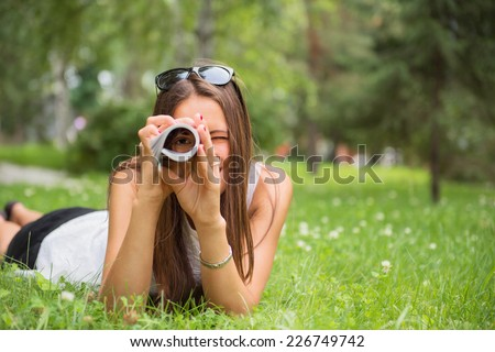 Young brunette woman enjoying the lying on the green grass in the garden and looking through rolled-up magazine - stock photo