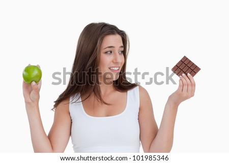 Young brunette woman holding a delicious piece of chocolate and a green apple - stock photo