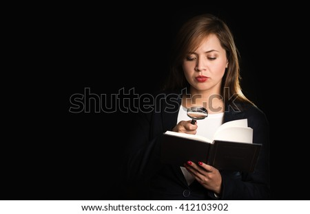 Young brunette woman holding open book and reading using magnifying glass, black background - stock photo